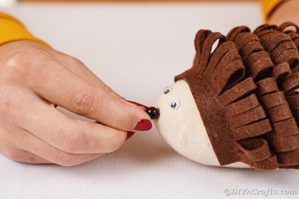 Hand gluing bead onto front of stuffed sock