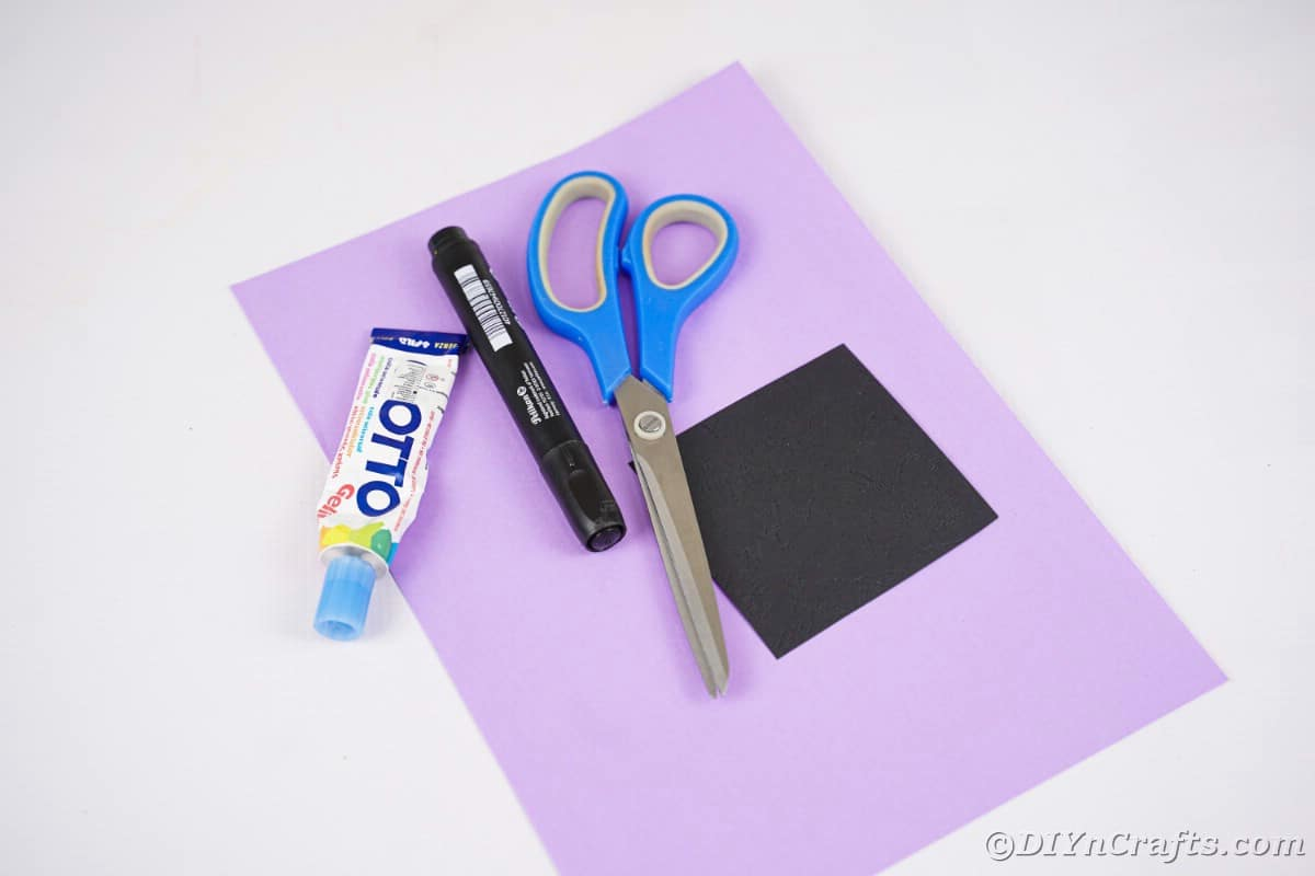 Purple paper on white table topped with scissors glue and marker
