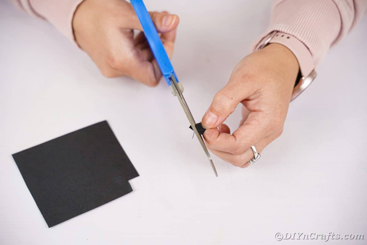Woman cutting small circle of black paper