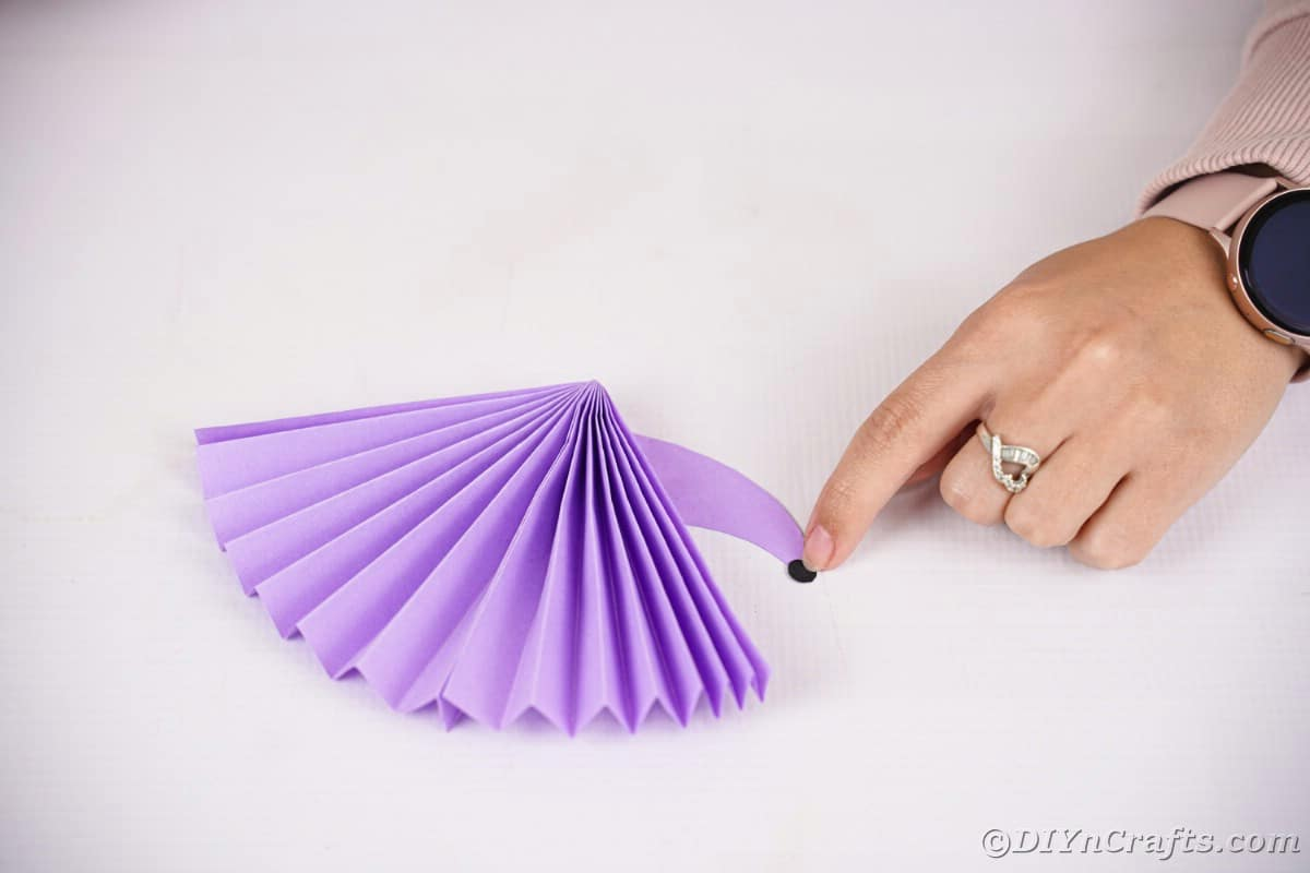 Hand gluing black nose to purple paper