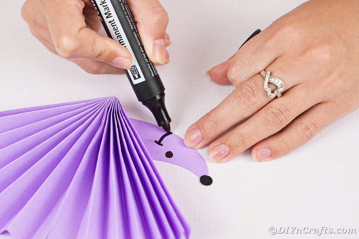 Hand drawing smile onto hedgehog face on purple paper