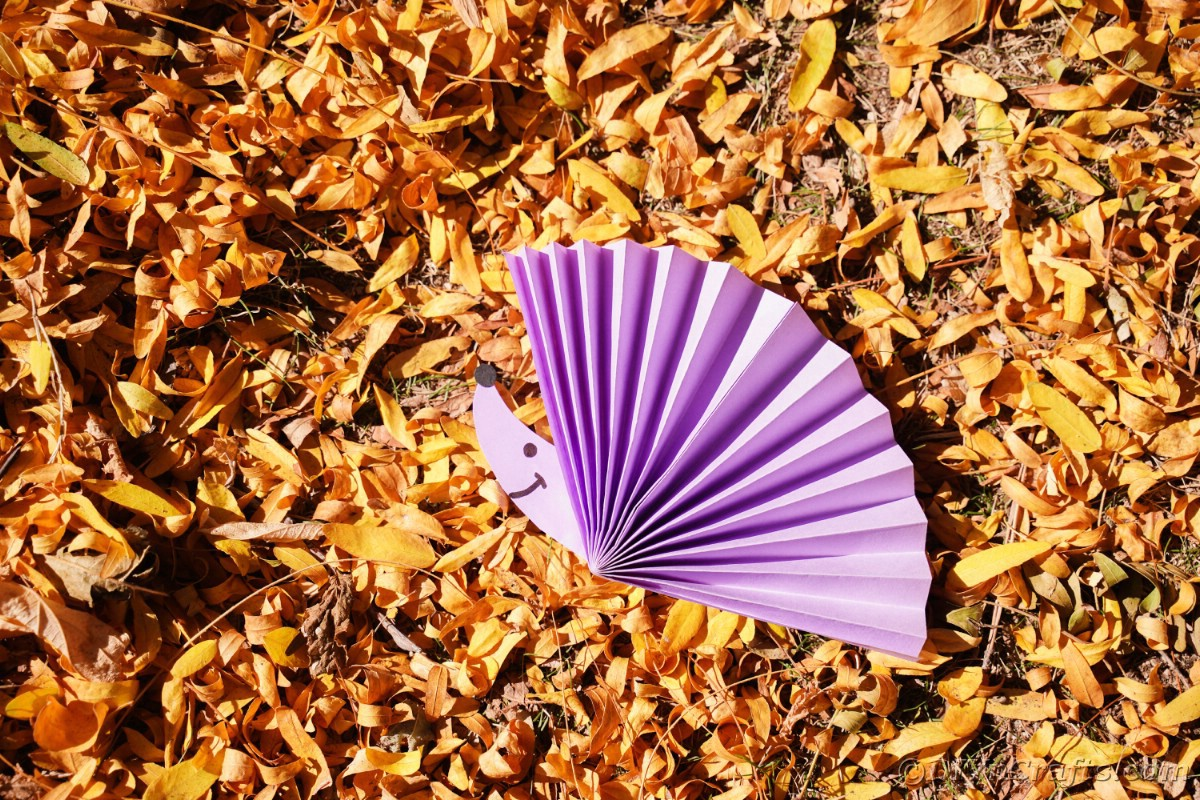 Dry leaves with purple fake hedgehog on top