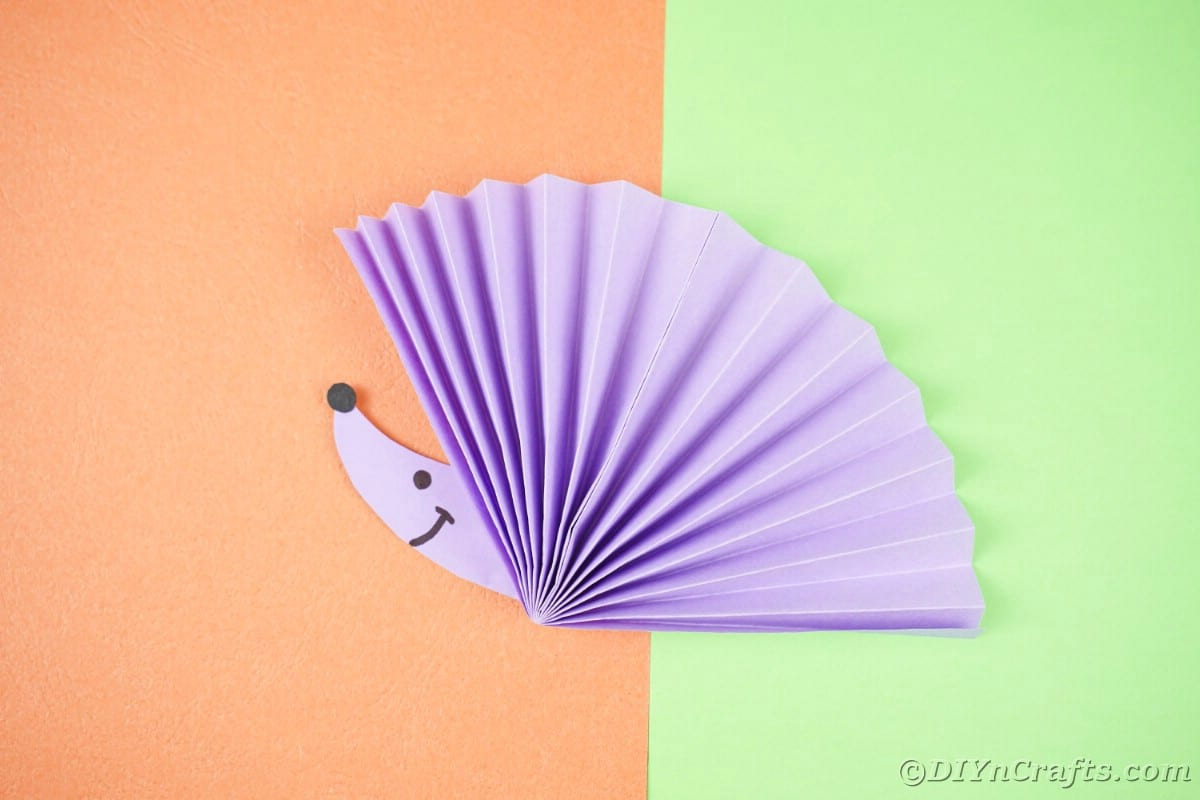 Green and orange background with bright purple paper fan with hedgehog face on top
