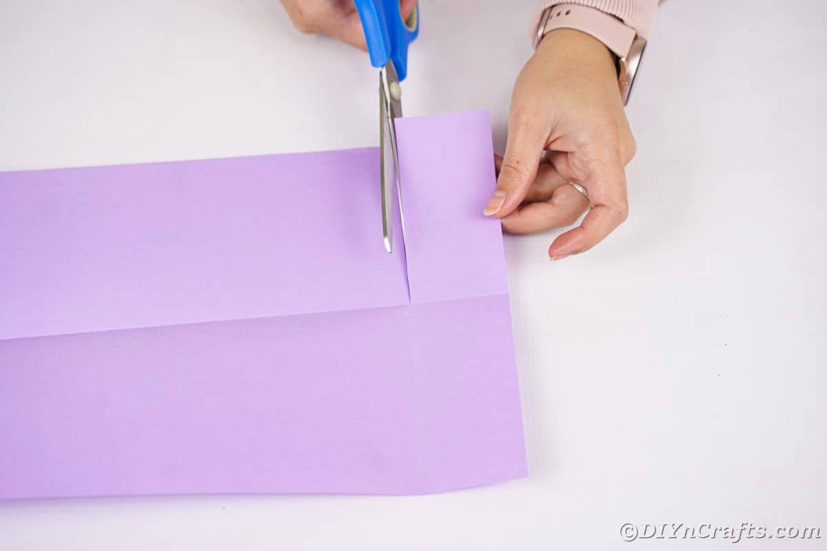 Hand cutting paper with blue scissors