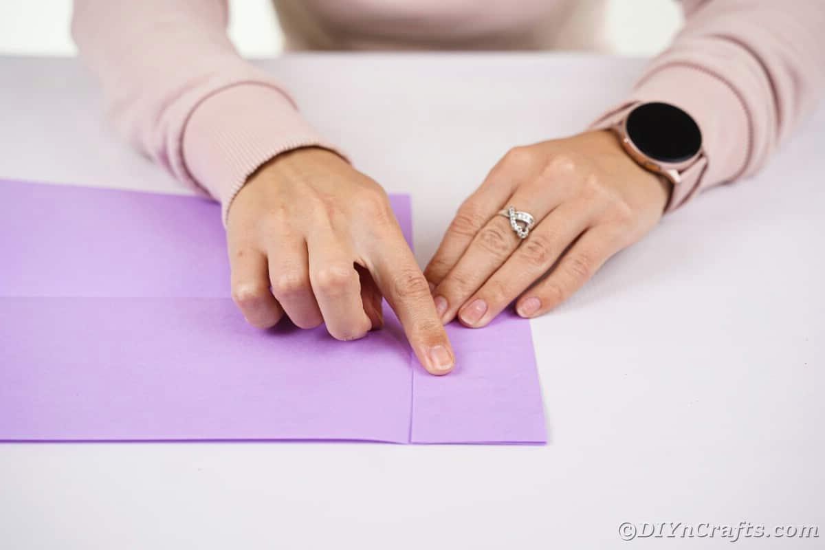Womans hands folding purple paper