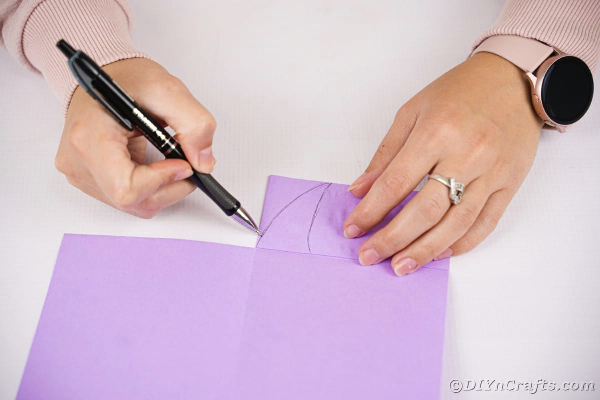 Hand drawing shape onto paper