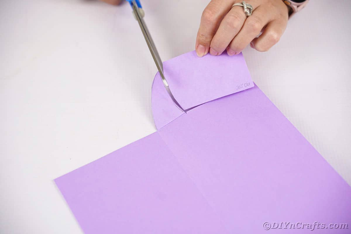Hand cutting shape out of purple paper
