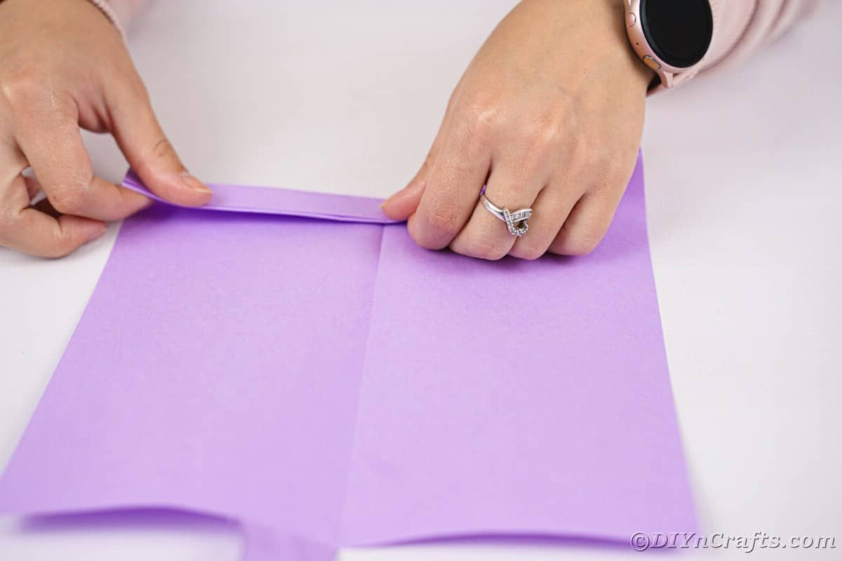 Two hands folding paper