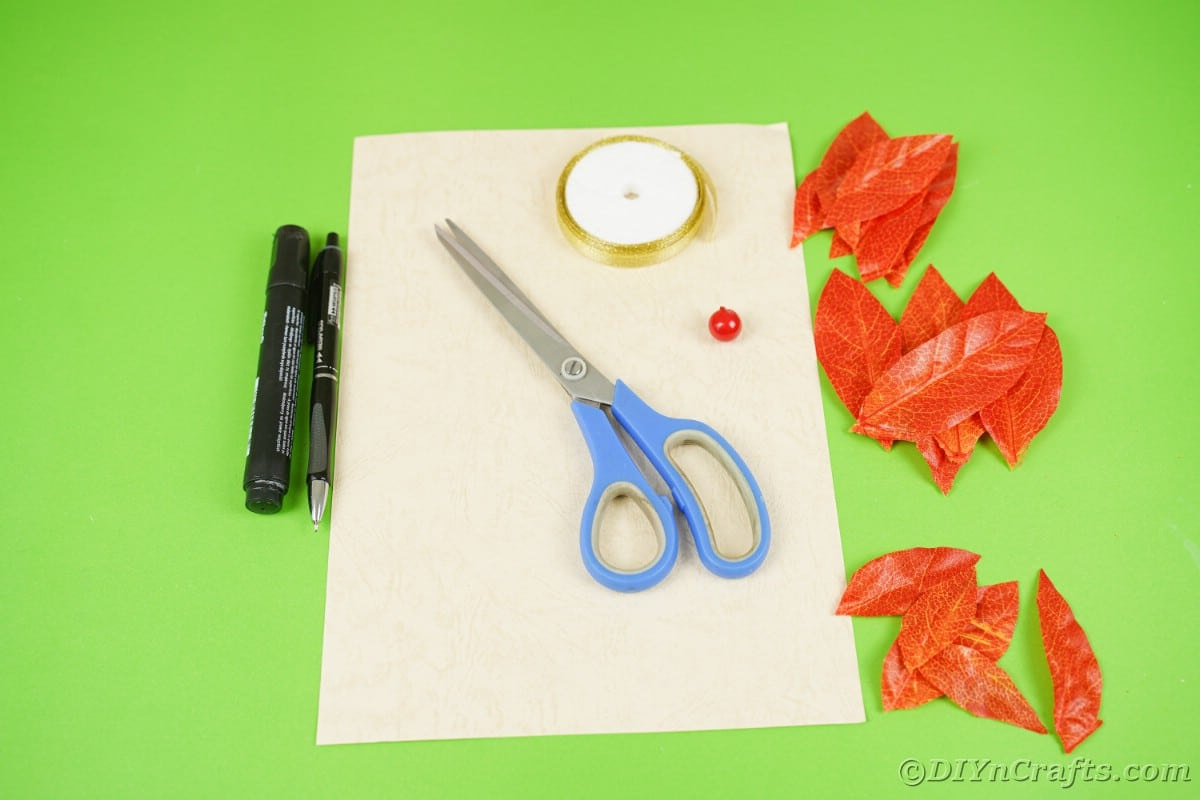 Cream paper scissors markers and orange fake leaves on green surface
