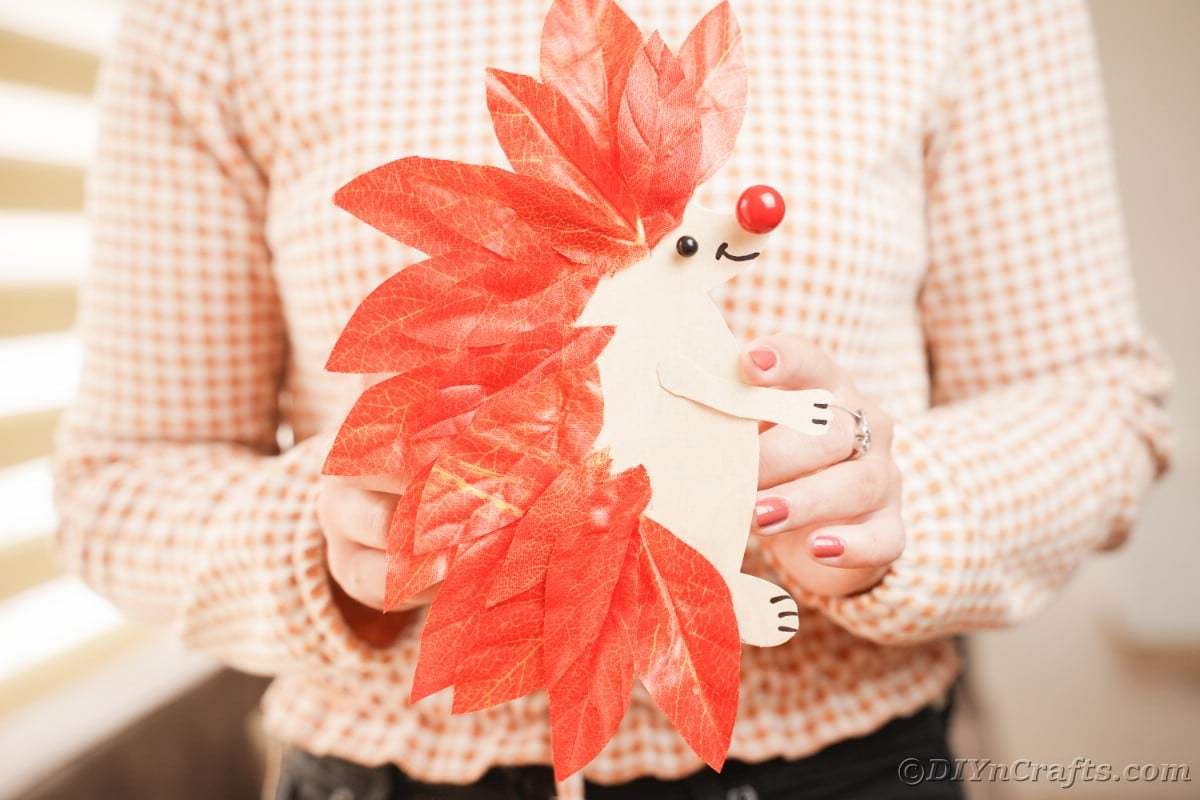 Hedgehog made of paper and fake leaves being held by woman