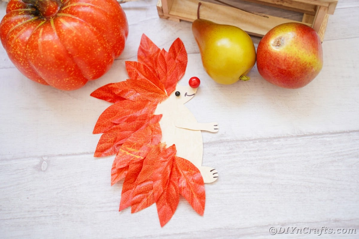 White wood surface with fake pumpkin and pears next to paper hedgehog