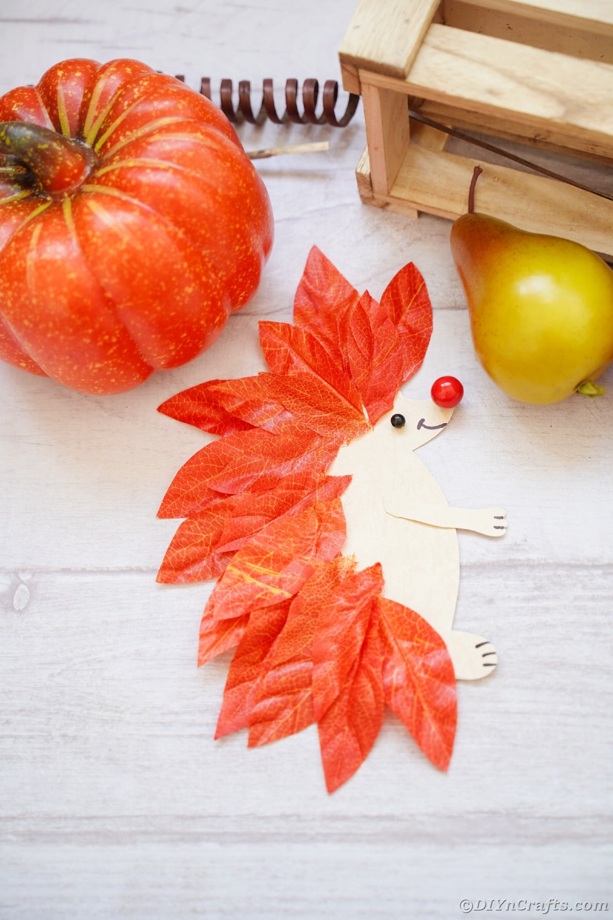 Paper and leaf hedgehog laying on white wood slat