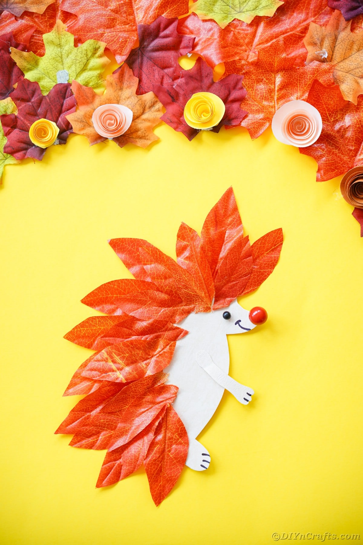 Hedgehog made of paper and fake leaves laying on yellow surface