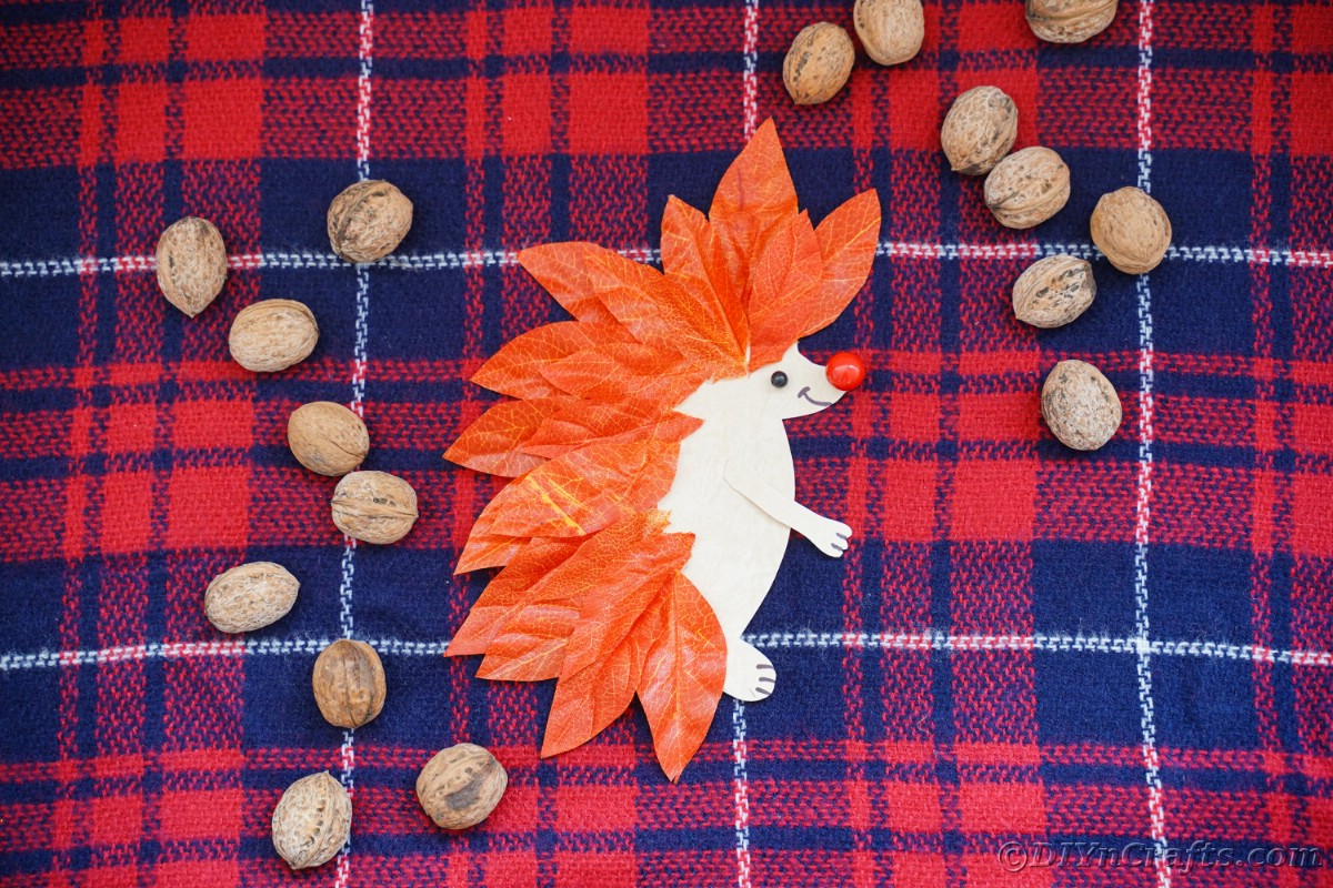 Paper hedgehog with whole pecans around it laying on plaid fabric