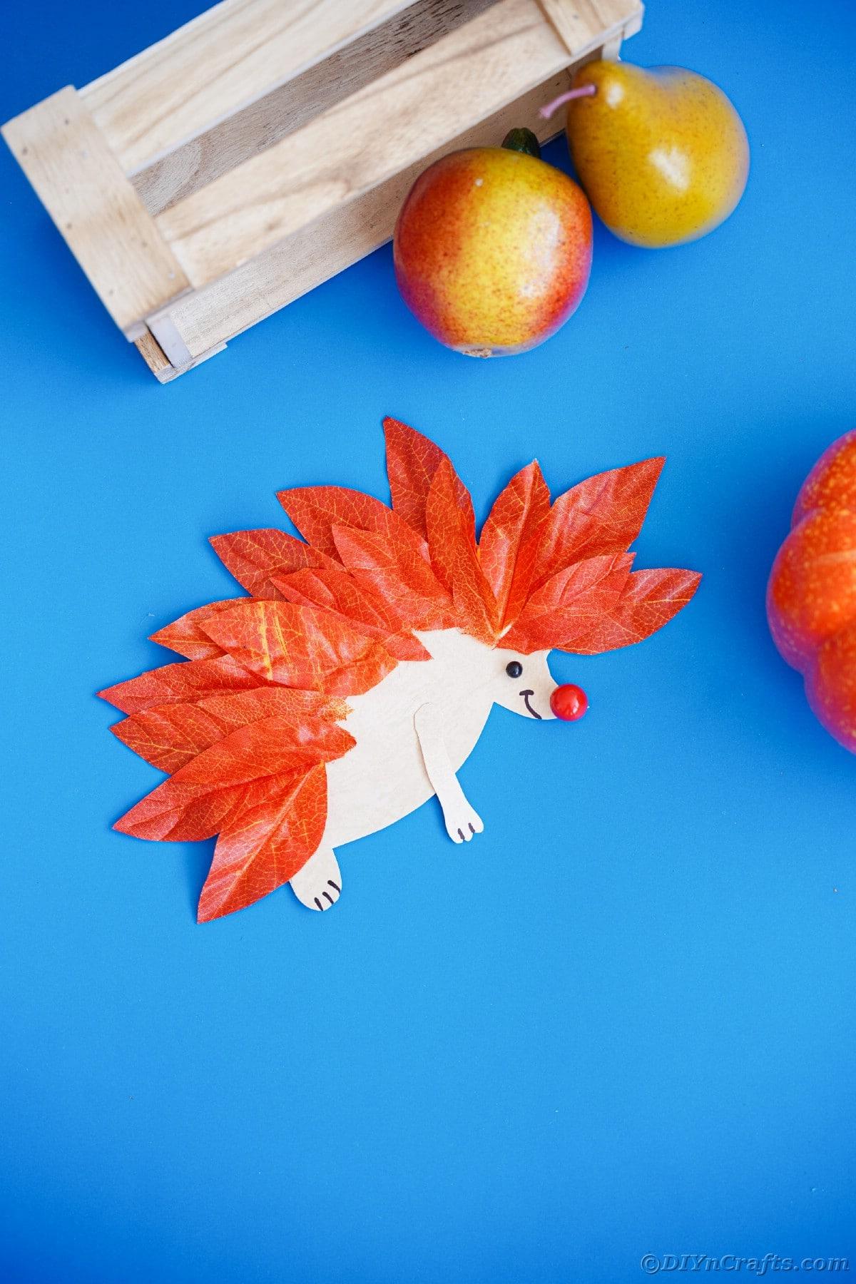 Mini paper hedgehog on blue table