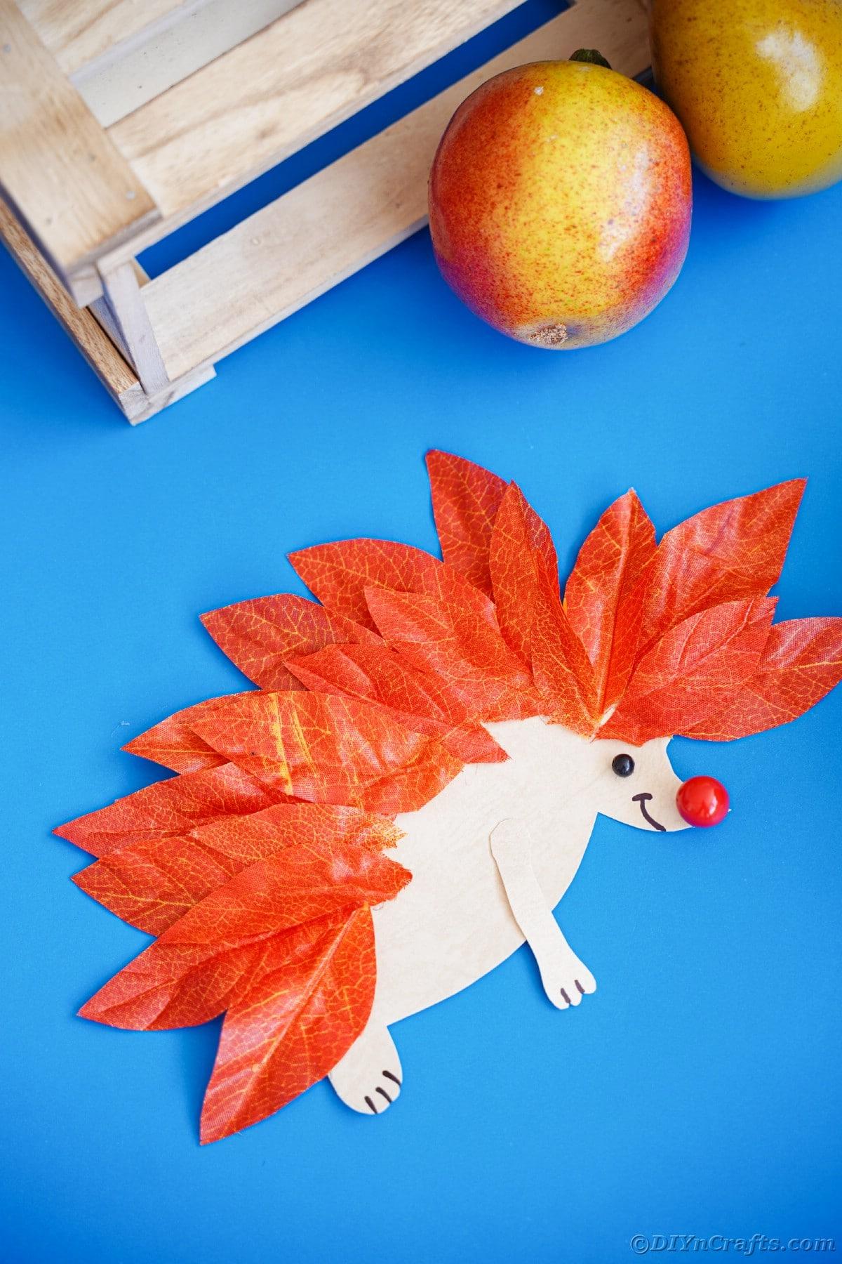 Fake leaf hedgehog on blue paper