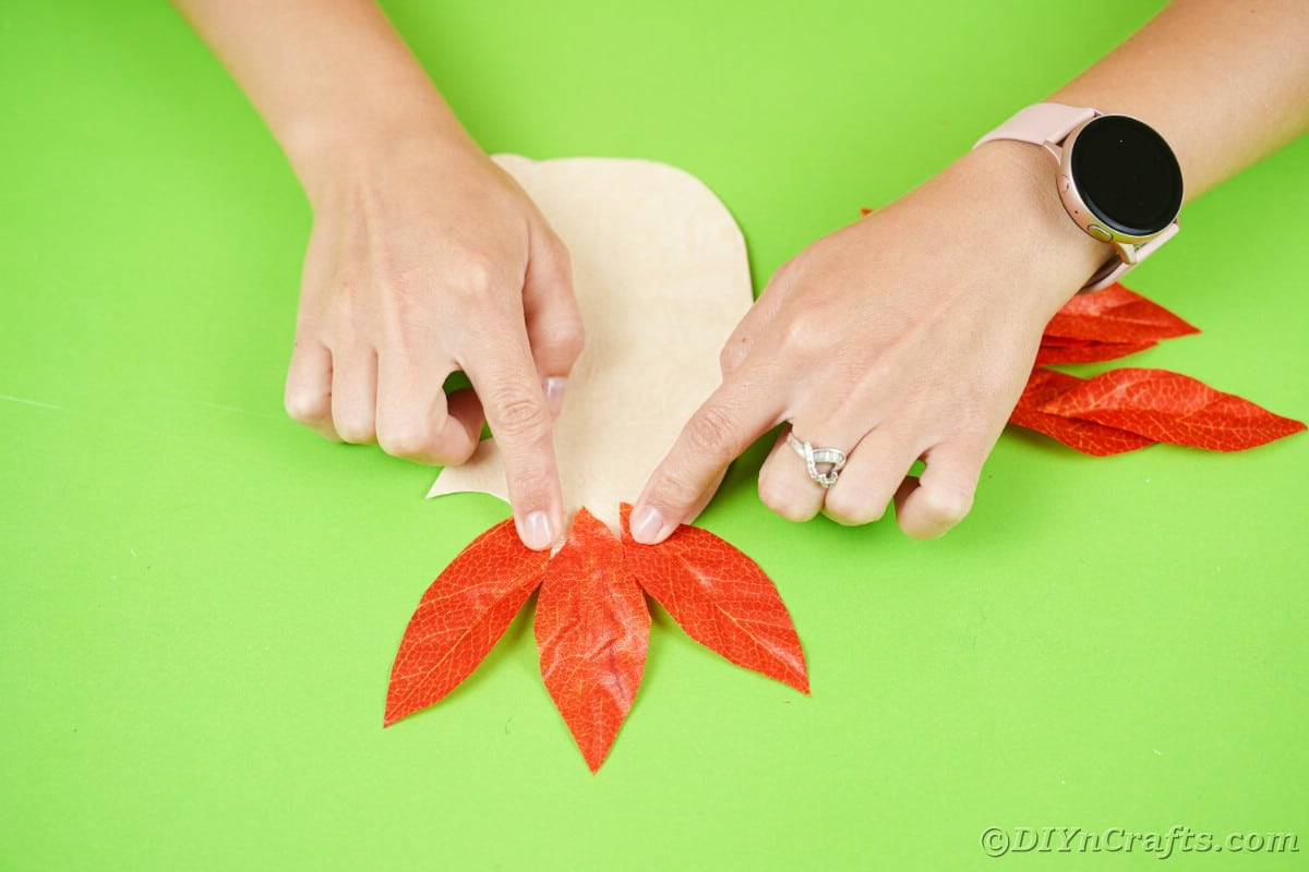 Hands holding three fake leaves on top of cream paper