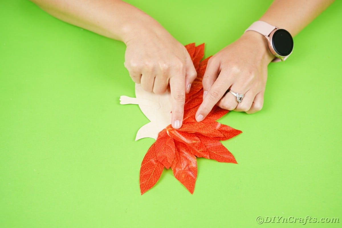 Hands holding fake leaves down on top of hedgehog shaped paper