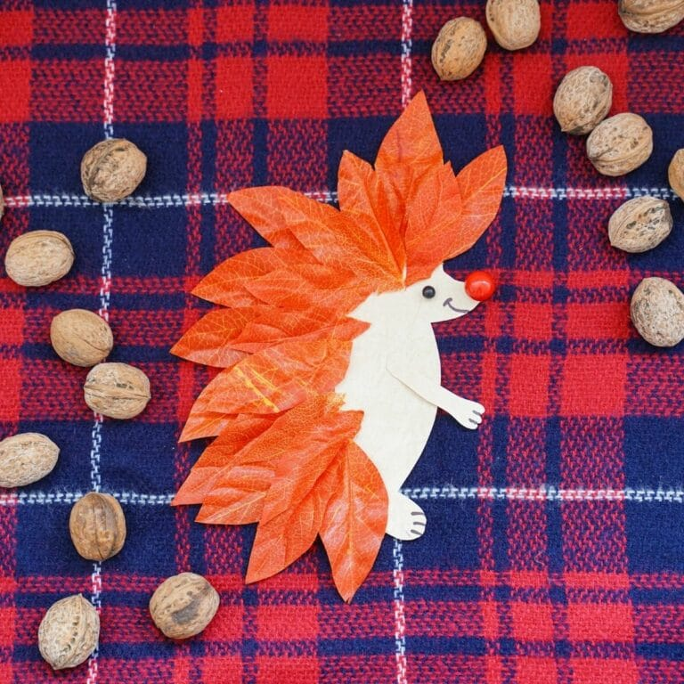Red and blue plaid fabric with paper and leaf hedgehog on top next to pecans