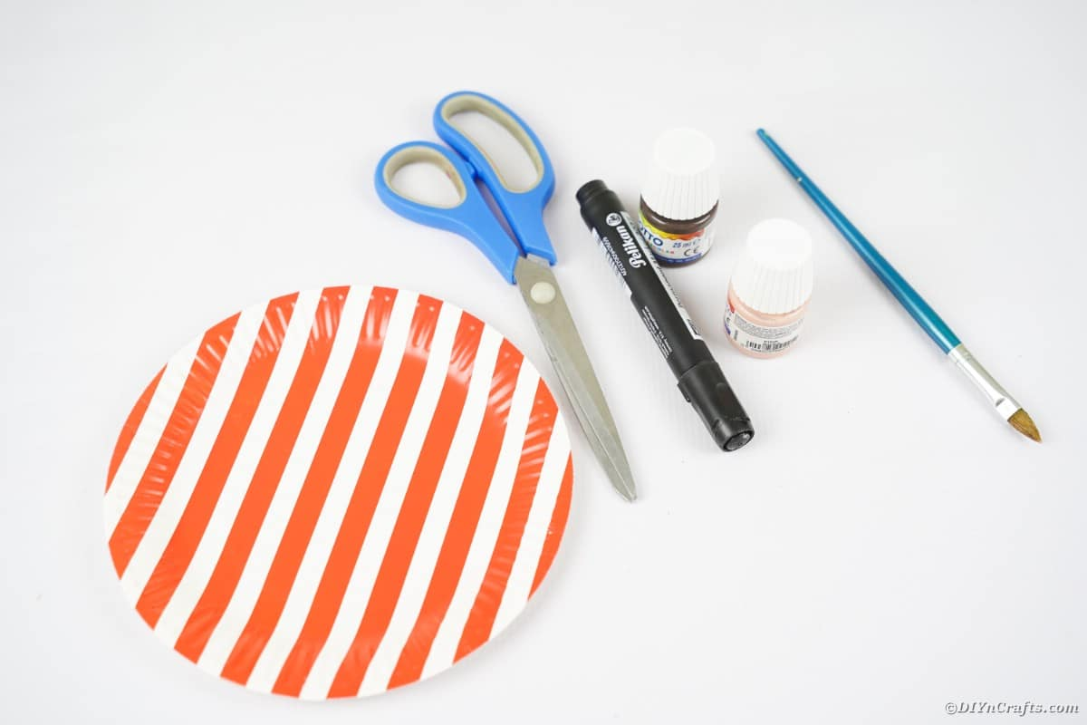 Striped plate with scissors marker and paint on white table