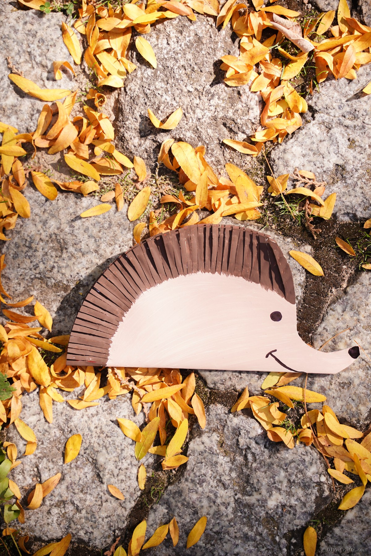 Paper hedgehog decoration on cobblestones with dry leaves