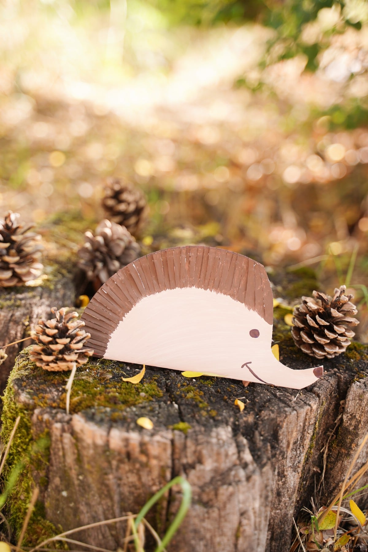 Hedgehog craft sitting on moss and pinecone covered stump