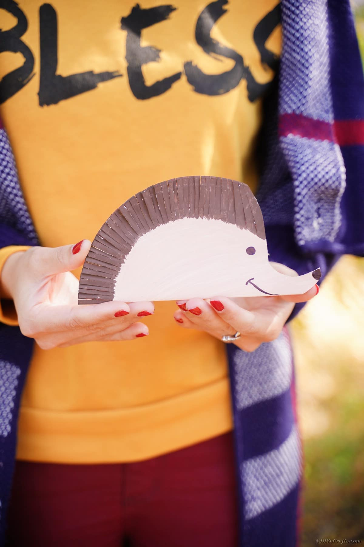 Woman in orange shirt holding a paper plate hedgehog
