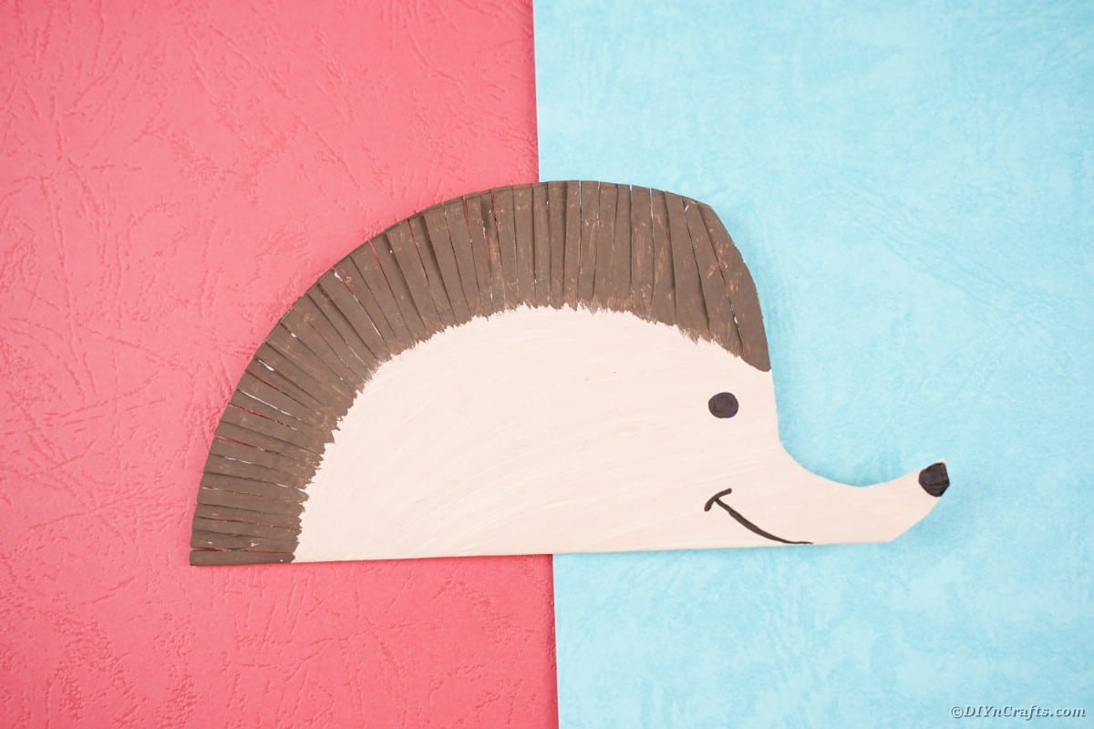 Paper plate hedgehog sitting on pink and blue paper