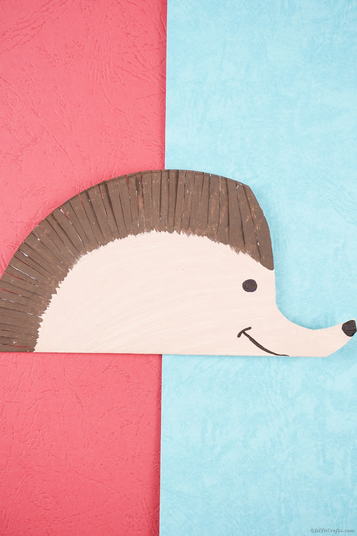 Paper plate hedgehog laying on pink and blue paper