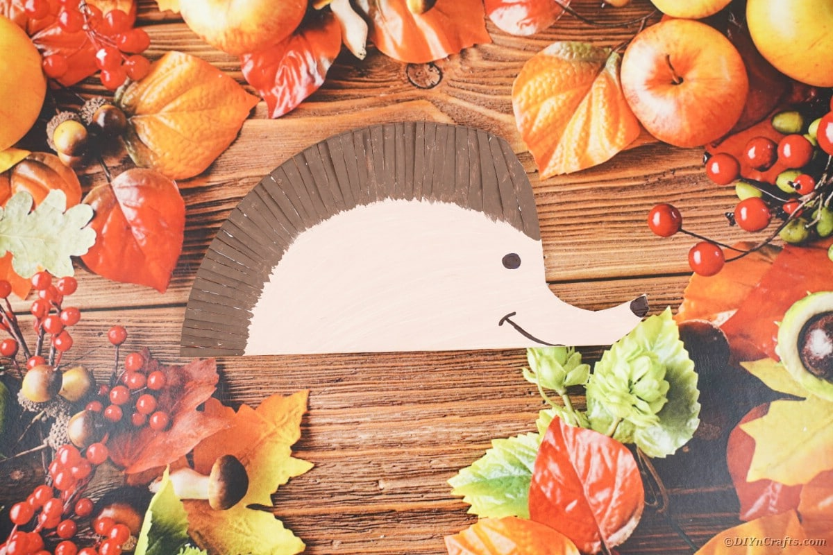 Fake leaves and paper hedgehog on wood table