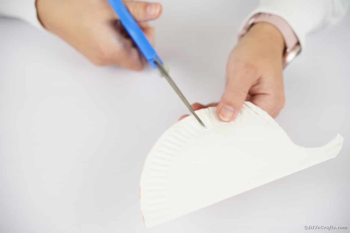Hand using scissors to cut top of paper plate