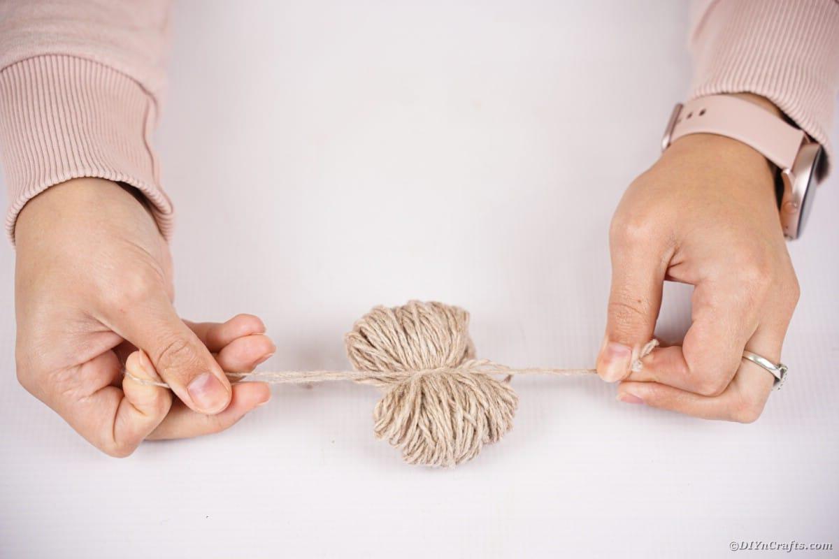 Mani che legano un fascio di filo al centro