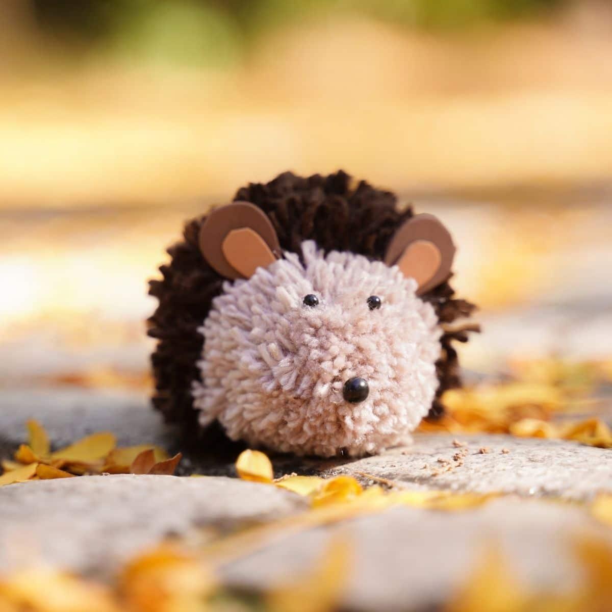 Toy hedgehog sitting on rock