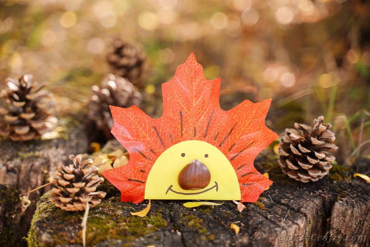 artificial leaf with yellow face sitting up on stump