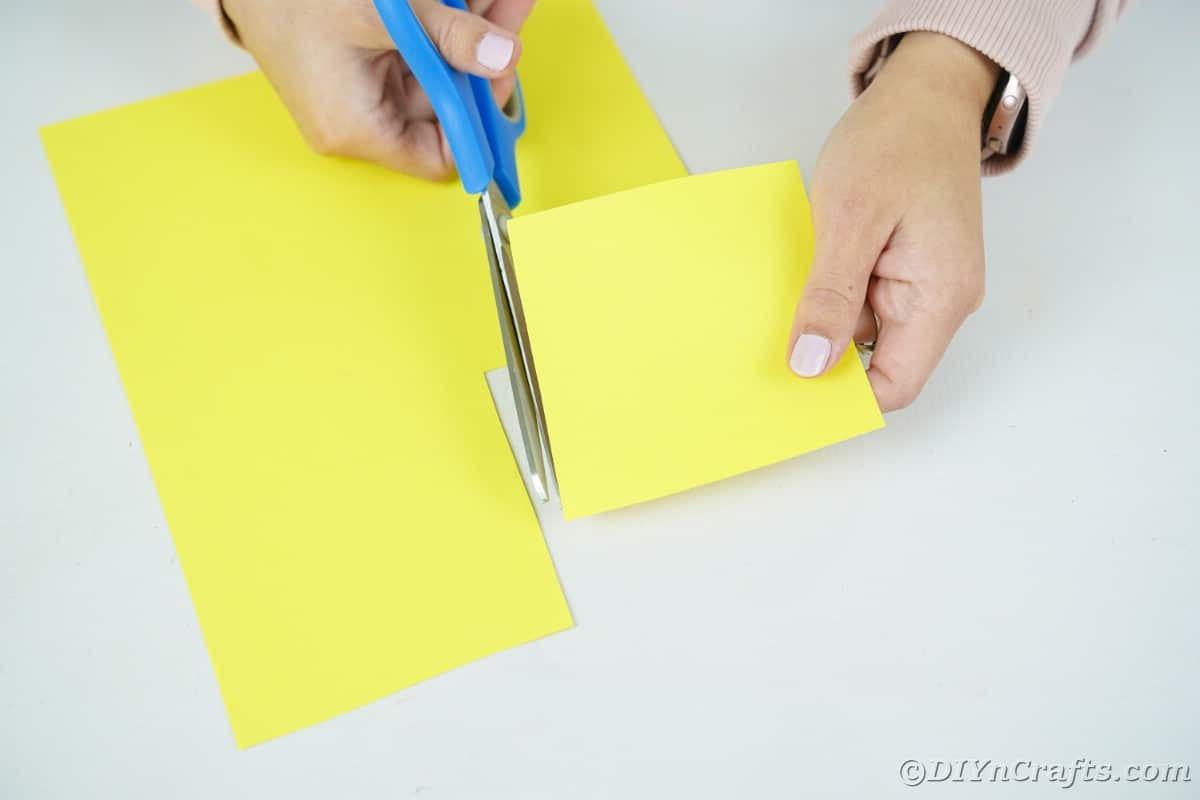 Hands cutting yellow paper