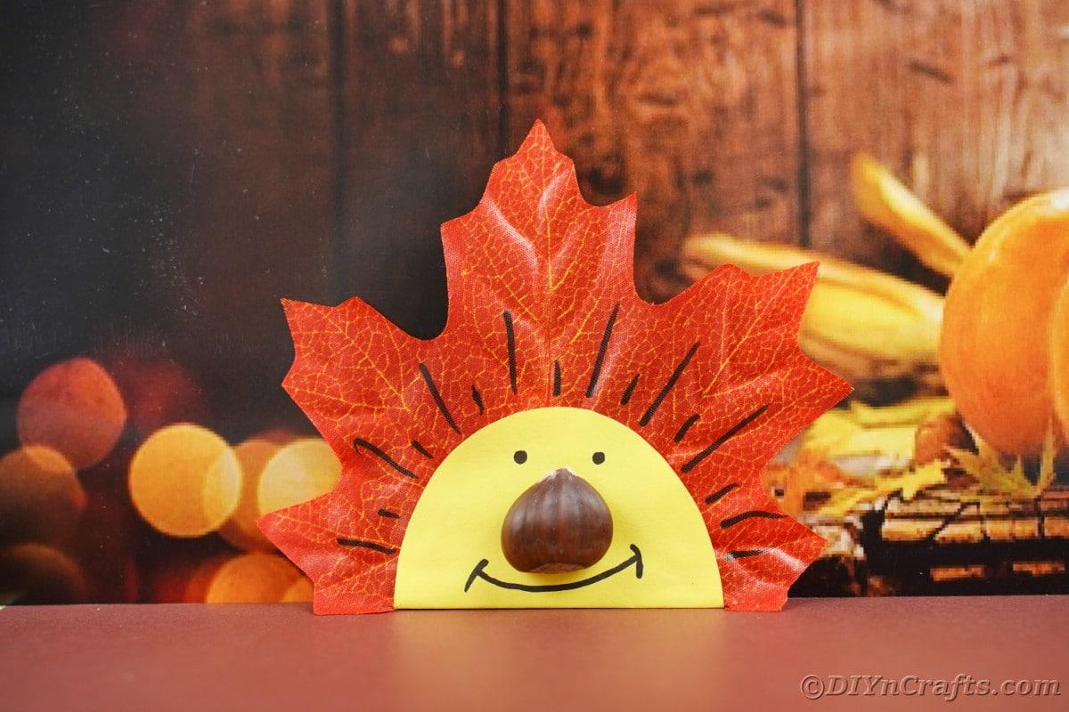 Smiling leaf face in front of pumpkin banner