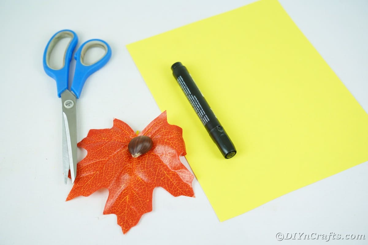 Orange fake leaf and yellow paper with marker and scissors on white table