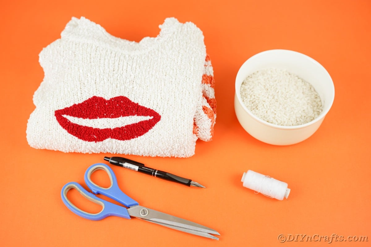 Tigela de suéter branco com arroz e tesoura na mesa laranja