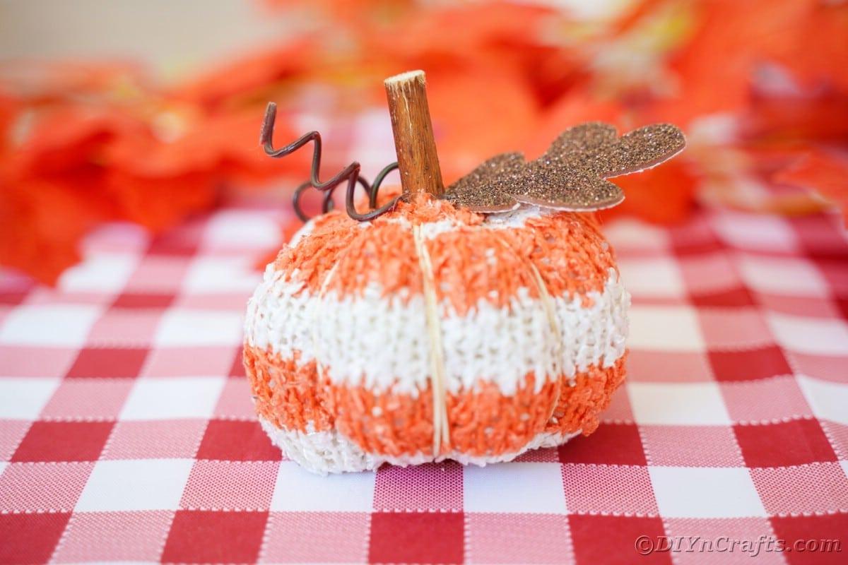 Abóbora listrada de laranja e branco em toalha de mesa quadriculada