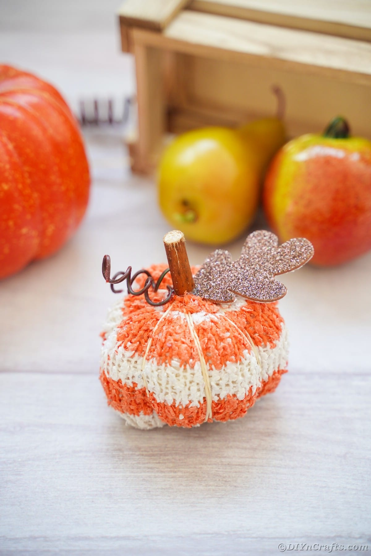 Abóbora de tecido listrado laranja e branco na mesa branca