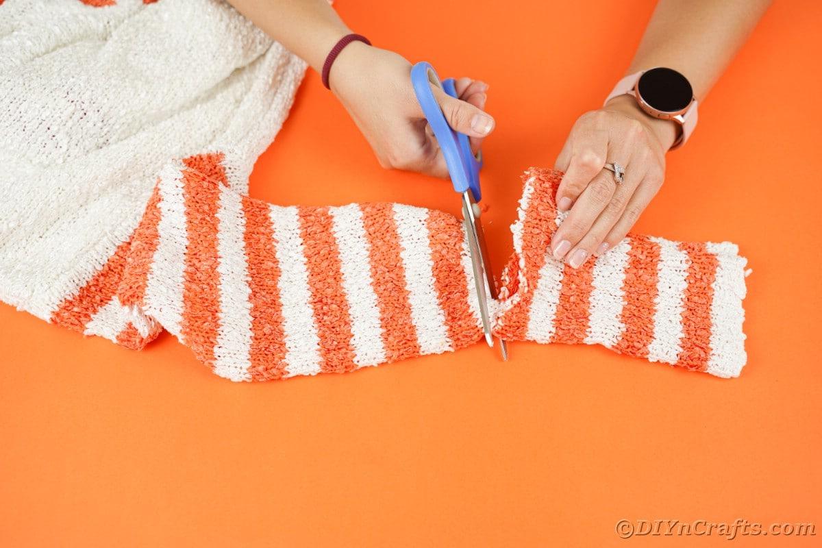 Corte a mão da manga do suéter com uma tesoura azul