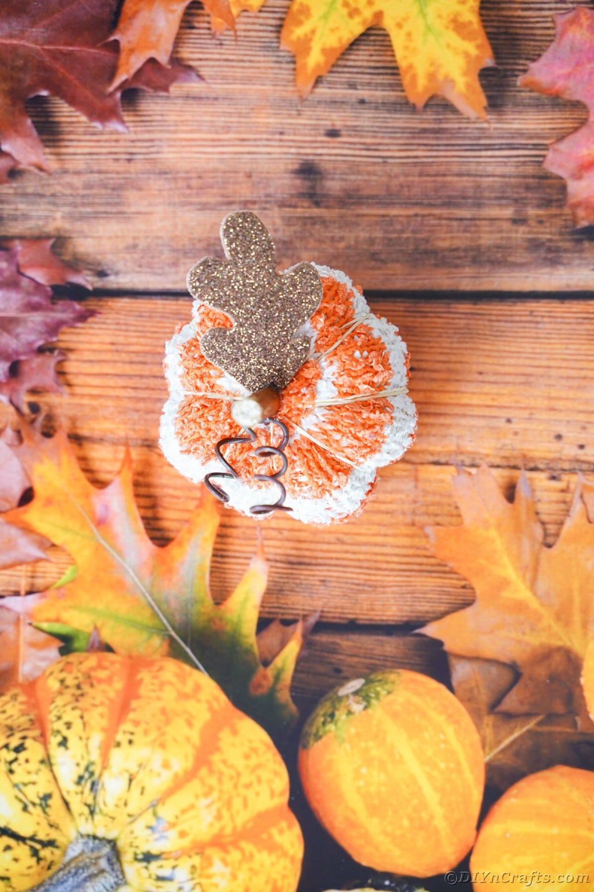 Abóbora de tecido listrado sentada em papel sazonal de outono