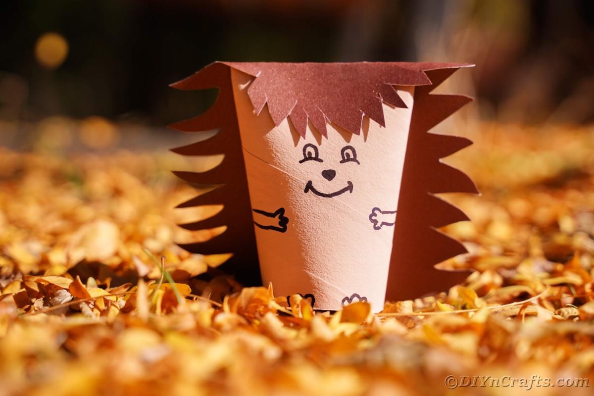 Toilet paper hedgehog sitting in pile of leaves