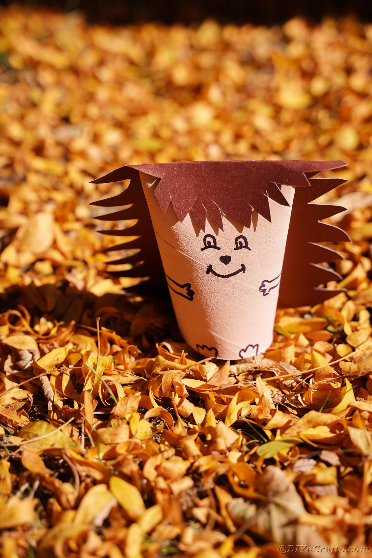 Fallen yellow leaves with paper hedgehog in middle
