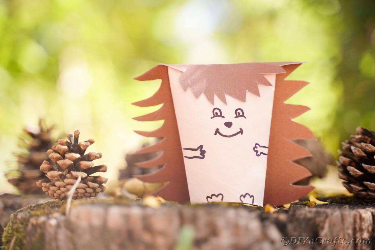 Light brown and dark brown paper hedgehog on stump