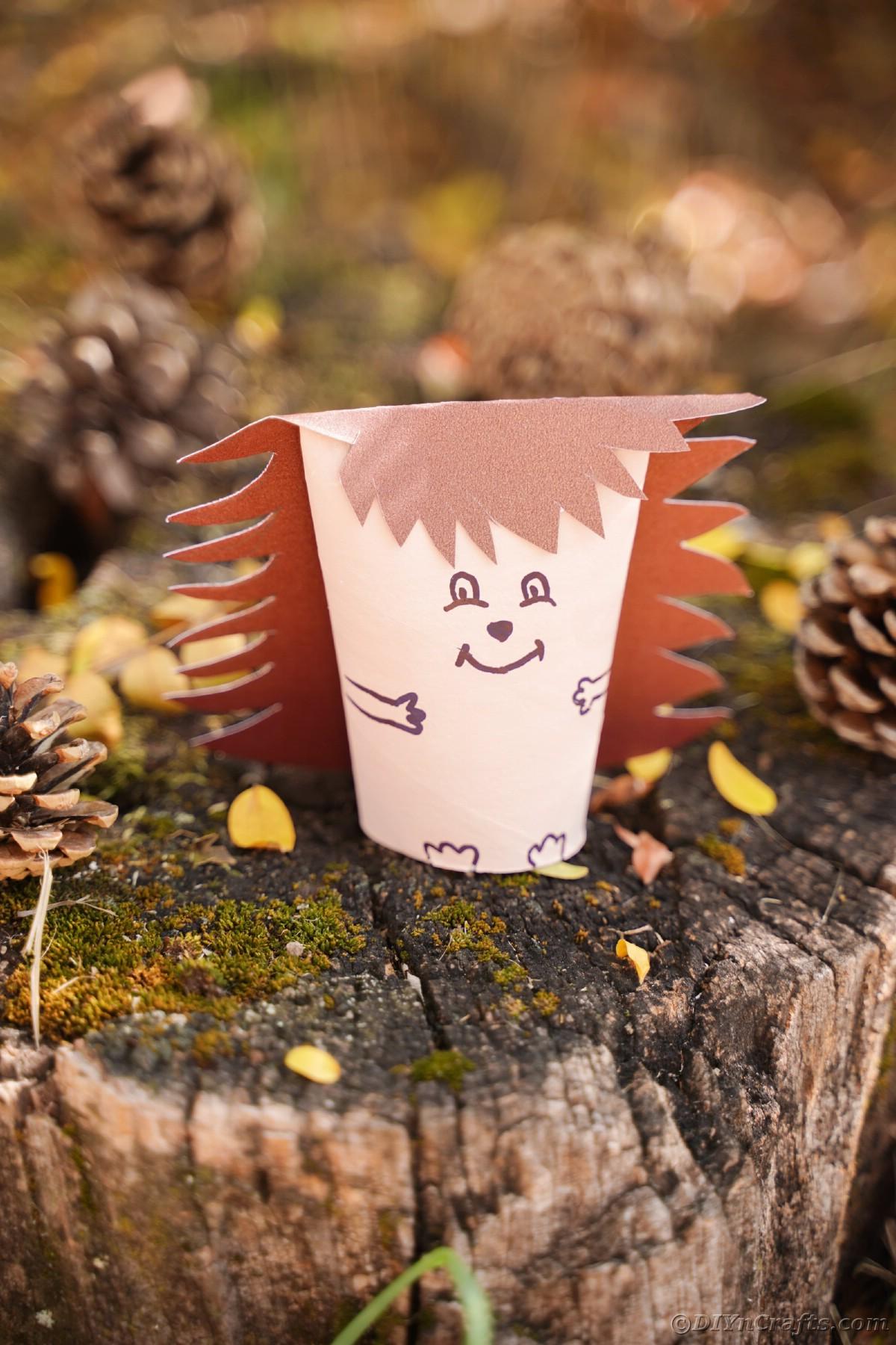 Paper hedgehog sitting on stump by pinecones