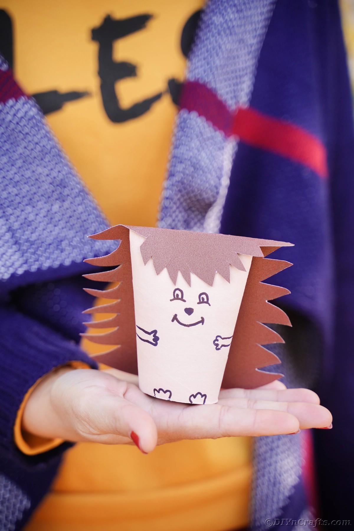 Woman in orange shirt holding toilet paper roll hedgehog