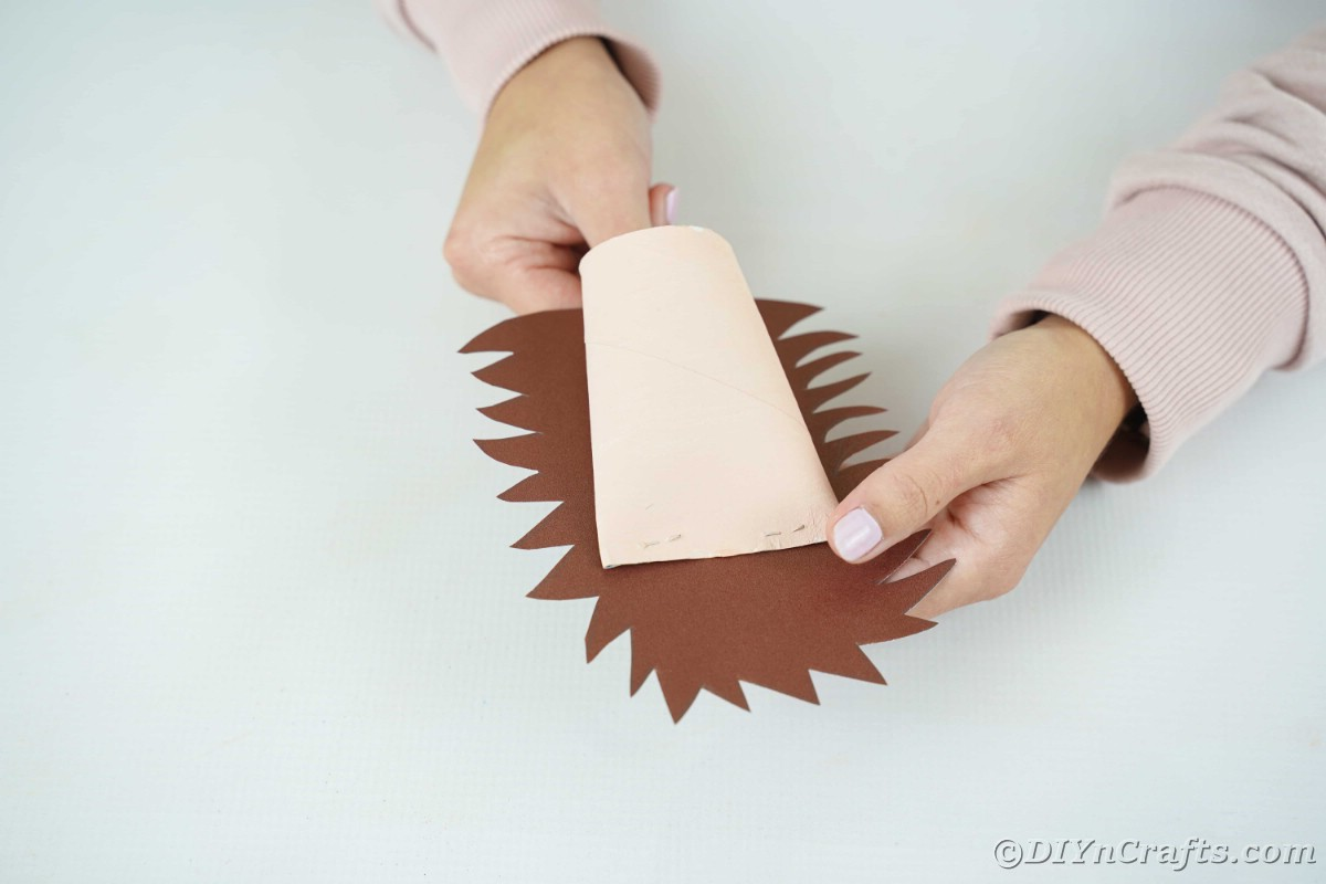 Gluing dark brown paper to painted toilet paper roll