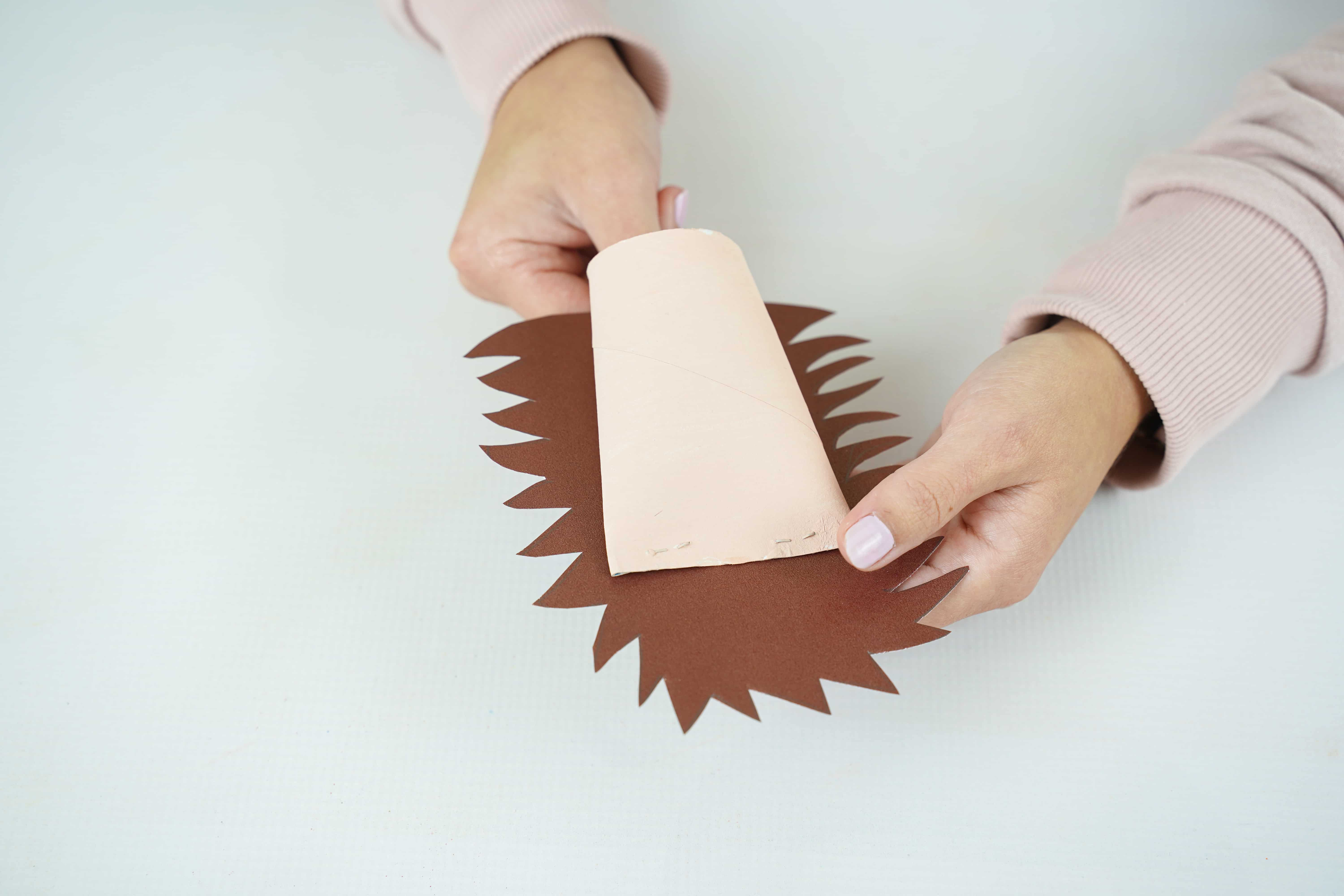 Hands gluing brown paper onto the light brown paper roll