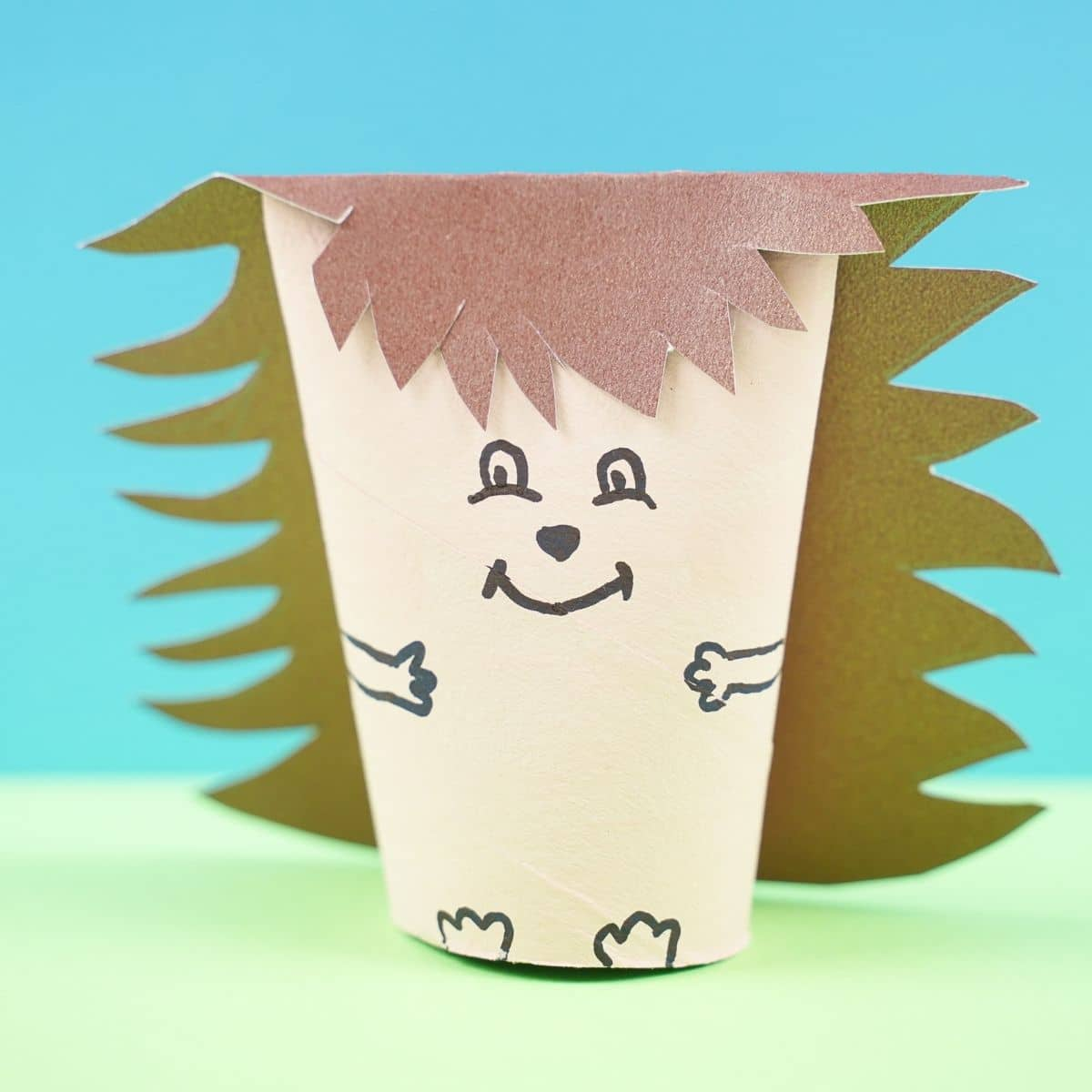 Mini paper hedgehog on green paper with blue background